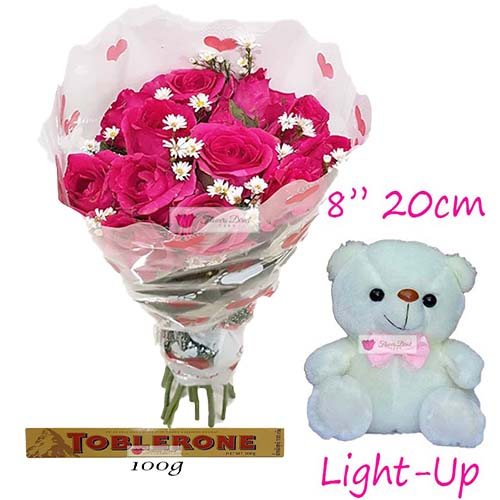 "Budget Gift Cebu includes; 12 Pink Roses in a plastic decorated wrapper. 8"" Light up bear 100 gram Toblerone"